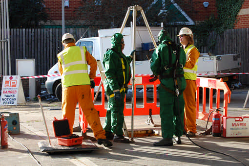 operative in full PPE with breathing apparatus and safety harness about to descend into a tank to clean it
