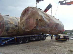 Tanks being loaded onto transport for disposal off-site
